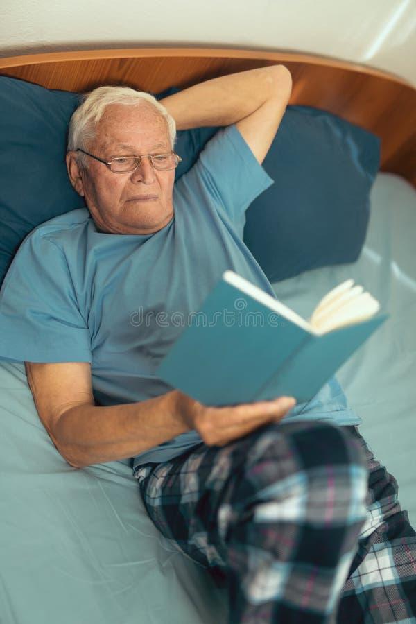 Homme supérieur se trouvant sur le livre du mauvais et de lecture photos libres de droits