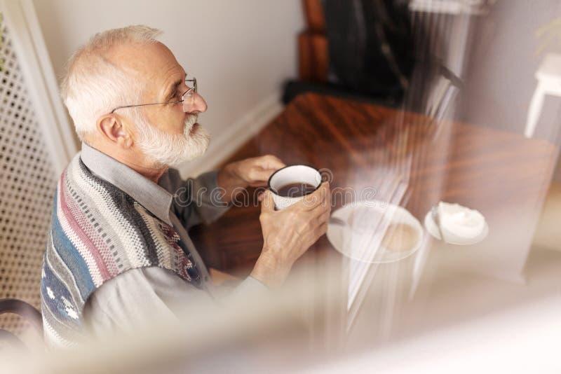Homme supérieur seul s'asseyant au thé potable de table de cuisine photos libres de droits
