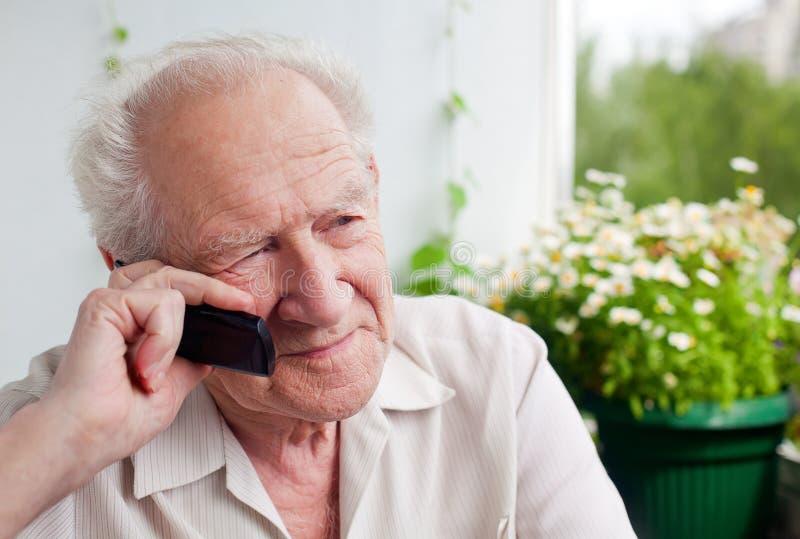 Homme supérieur songeur avec un téléphone photo stock