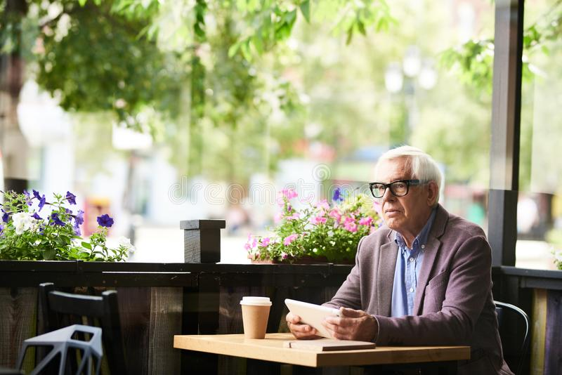 Homme supérieur songeur en café dehors photos stock
