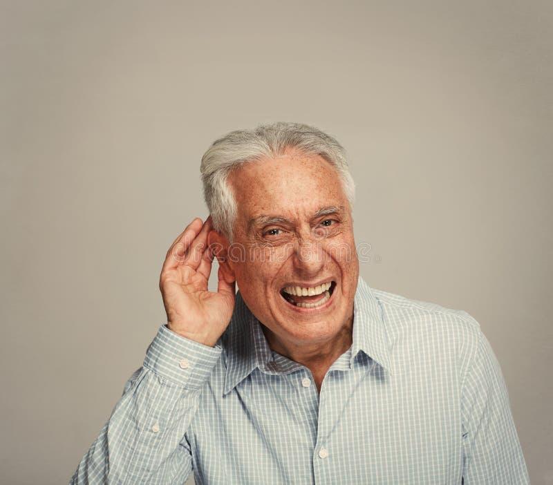 Homme supérieur sourd tenant la main près de l'oreille images stock
