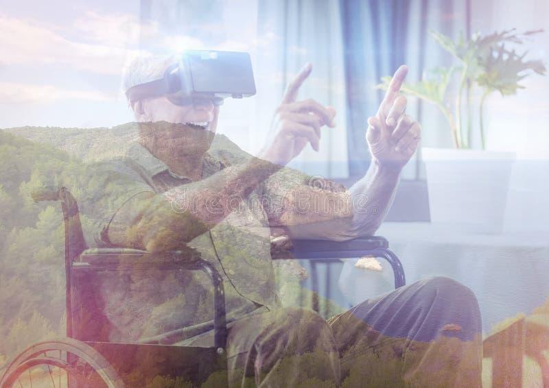 homme supérieur sur le fauteuil roulant avec des verres de VR dans les montagnes image stock