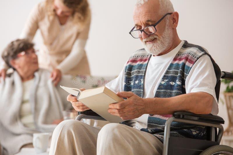 Homme supérieur sur le fauteuil roulant lisant un livre photo libre de droits