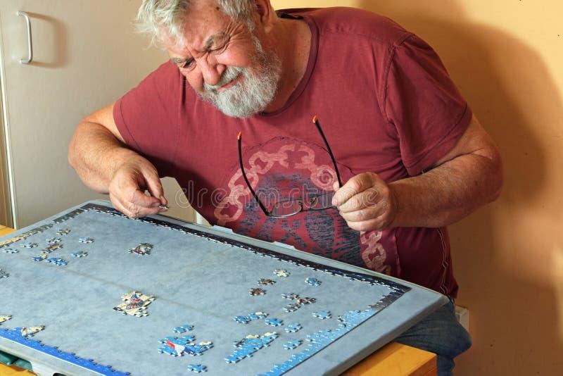 Homme supérieur sur son propre difficile faisant un puzzle denteux photo stock