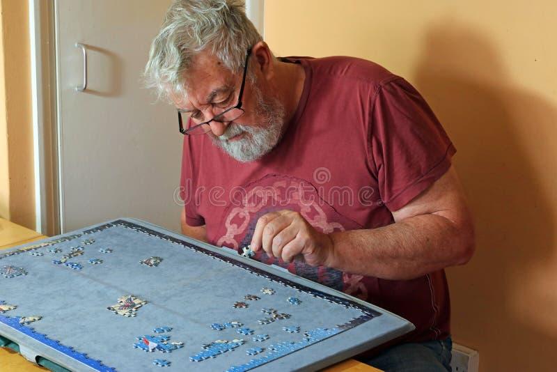 Homme supérieur sur son propre faire un puzzle denteux photographie stock libre de droits