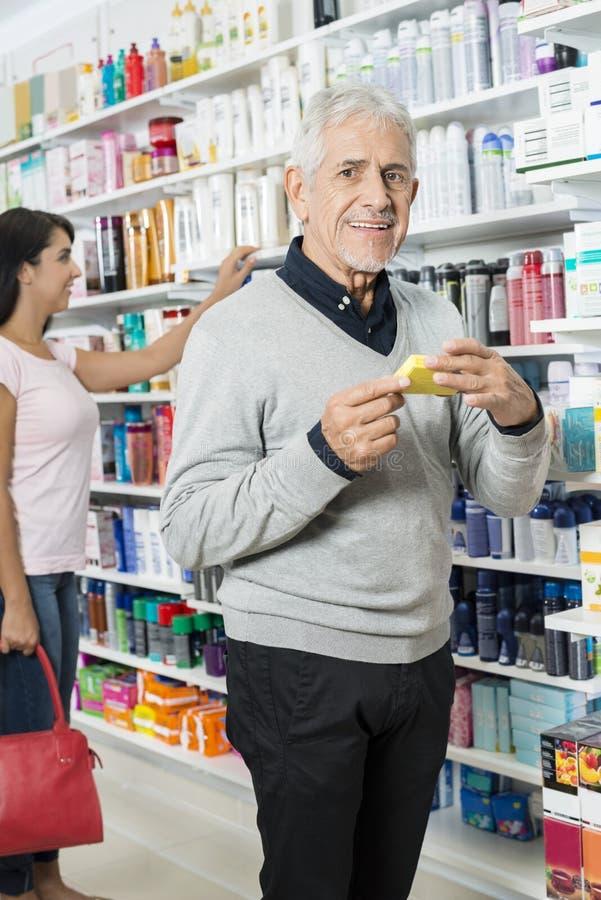 Homme supérieur tenant le produit tandis qu'achats femelles dans la pharmacie image stock