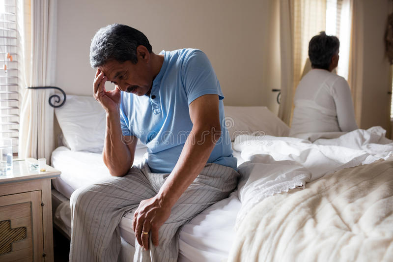 Homme supérieur tendu s'asseyant sur le lit photos stock
