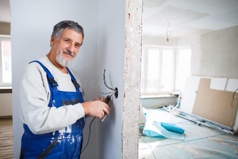 Homme supérieur travaillant aux installations électriques photo stock