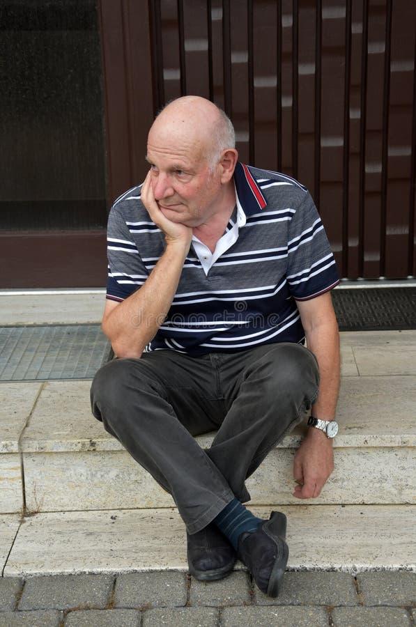 Homme supérieur verrouillé s'asseyant devant sa maison photographie stock libre de droits