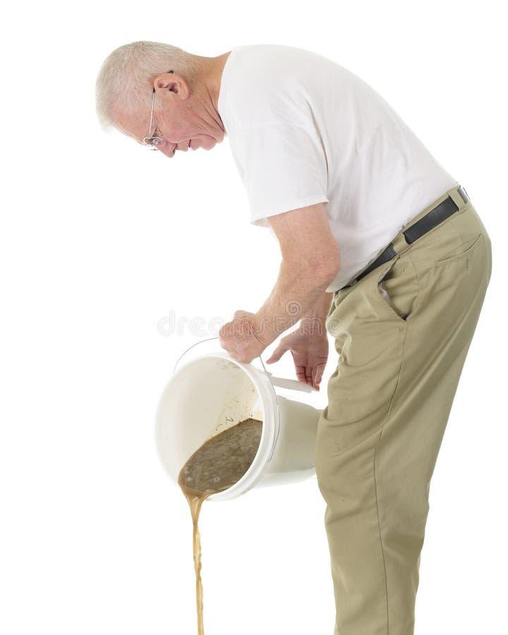 Homme supérieur vidant l'eau sale photos stock