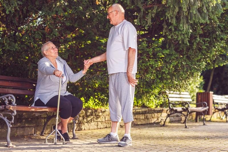 Homme supérieur vieillissant soutenant l'épouse malade en parc photos stock