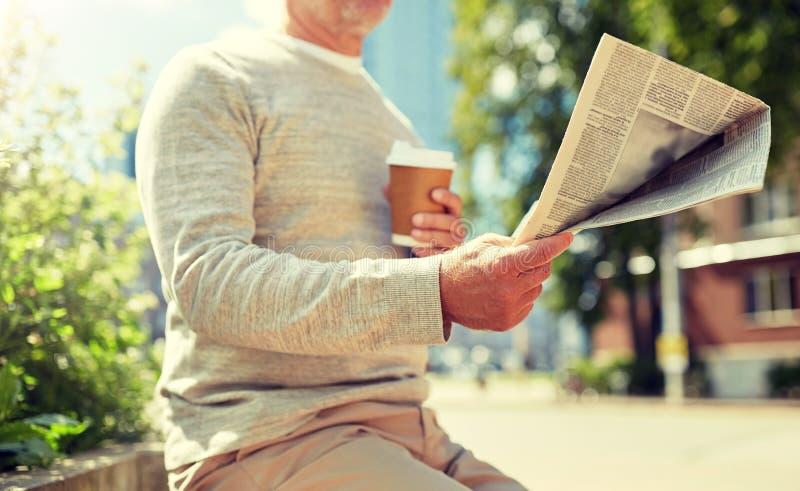 Homme sup?rieur avec le journal de lecture de caf? dehors photos stock