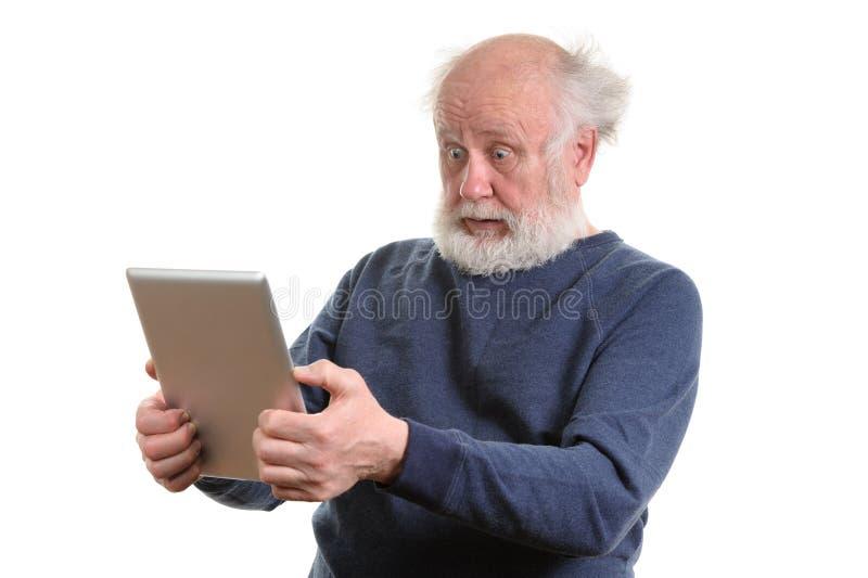 Homme sup?rieur choqu? dr?le utilisant la tablette d'isolement sur le blanc photo libre de droits