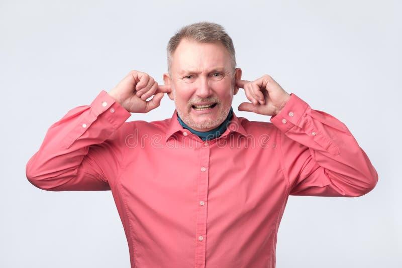 Homme sup?rieur dans la chemise rouge branchant des oreilles avec des doigts images stock