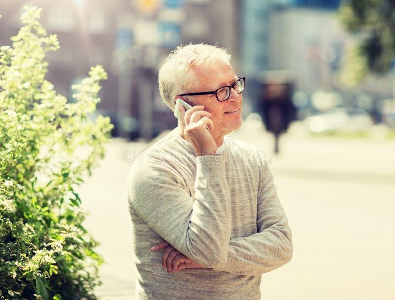 Homme sup?rieur heureux invitant le smartphone dans la ville images libres de droits