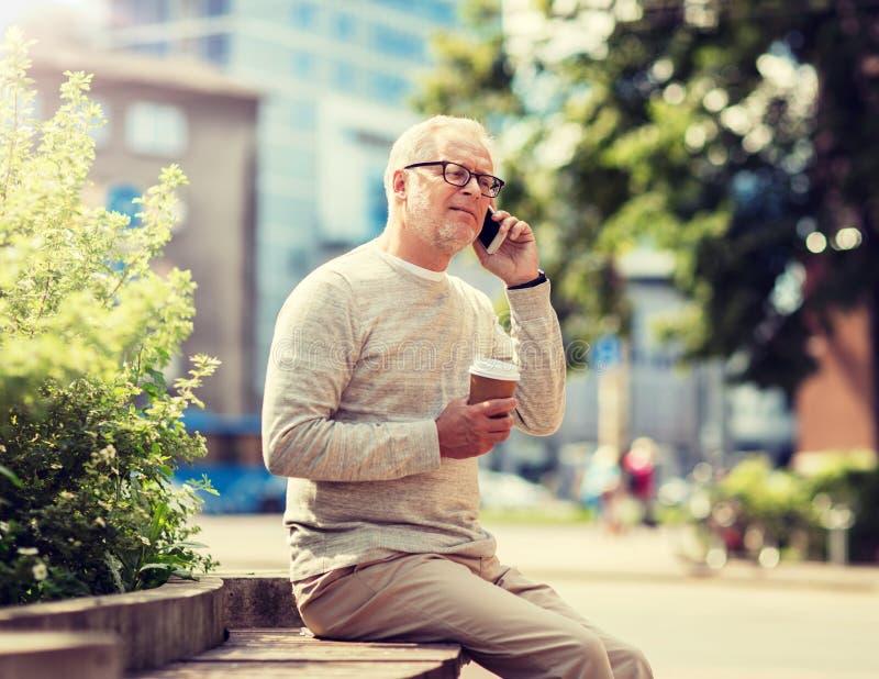 Homme sup?rieur heureux invitant le smartphone dans la ville images stock