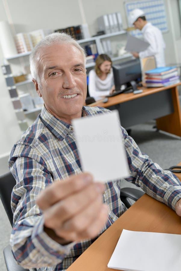 Homme supportant la carte de visite professionnelle de visite photos stock