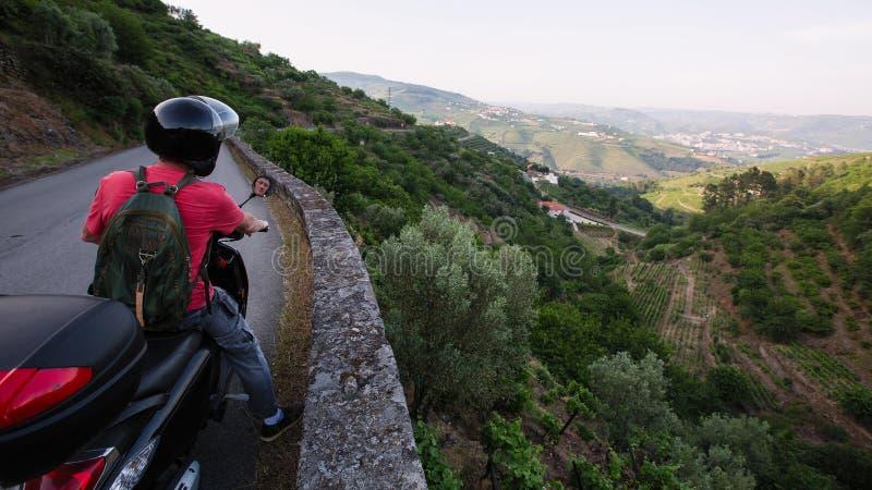 Homme sur des tours d'une motocyclette sur une route serpentine de la vallée de Douro, Porto photo libre de droits