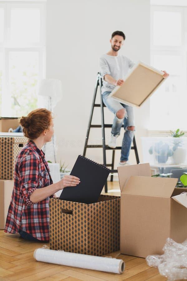 Homme sur l'échelle avec la substance d'emballage de peinture et de femme dans des boîtes tout en se déplaçant- photographie stock