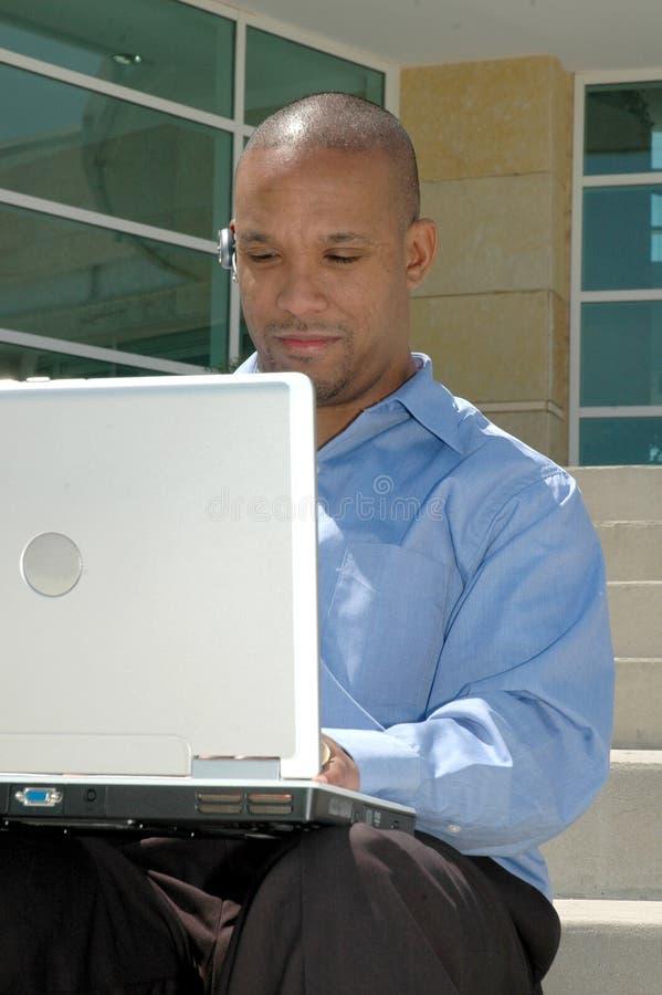 Homme sur l'ordinateur à l'extérieur image libre de droits