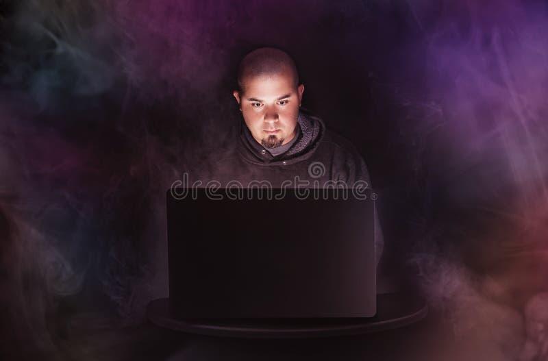 Homme sur l'ordinateur portable dans l'obscurité avec les lumières et la fumée colorées images stock