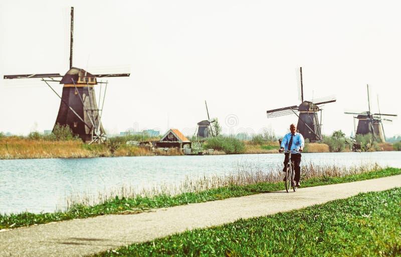Homme sur la bicyclette et les moulins à vent chez Kinderdijk, Pays-Bas photo libre de droits