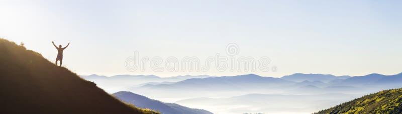 Homme sur la crête de la montagne Scène émotive Jeune homme avec le backpac photographie stock libre de droits