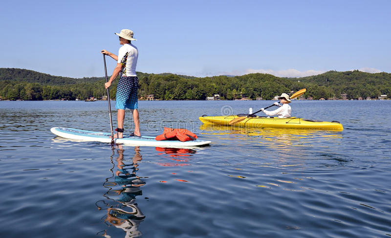 Homme sur la femme de Paddleboard sur le kayak image stock