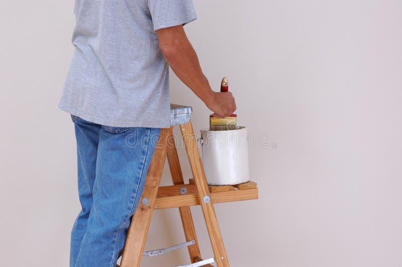 Homme sur la peinture d'échelle photo stock