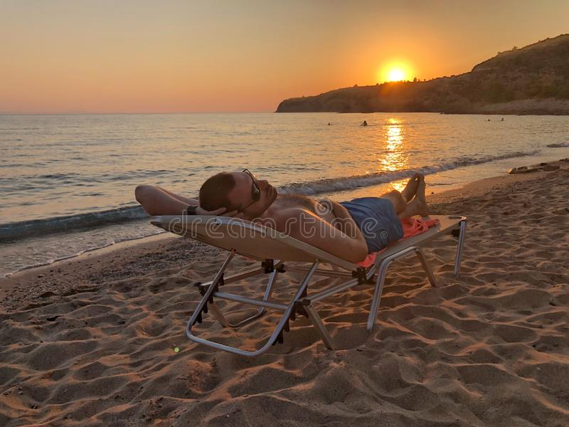 Homme sur la plage au coucher du soleil image libre de droits
