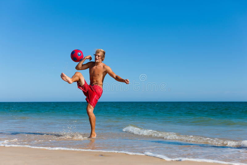 Homme sur la plage jouant au football images libres de droits