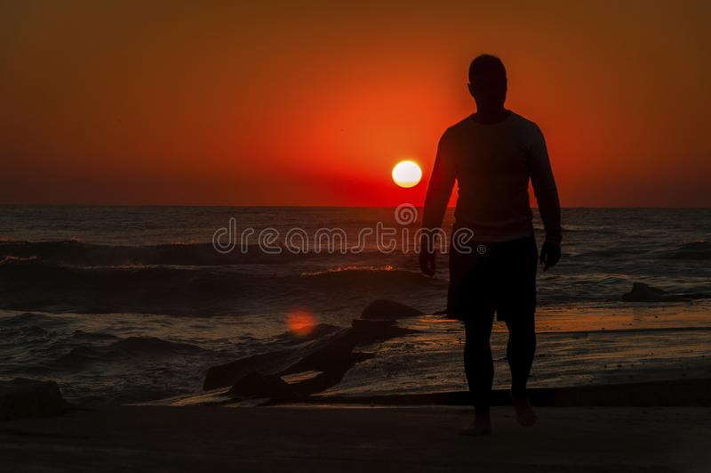 Homme sur la plage pendant le lever de soleil photographie stock