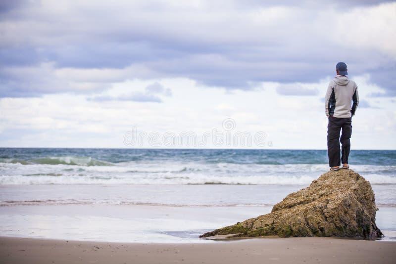 Homme sur la roche sur la plage sablonneuse images libres de droits