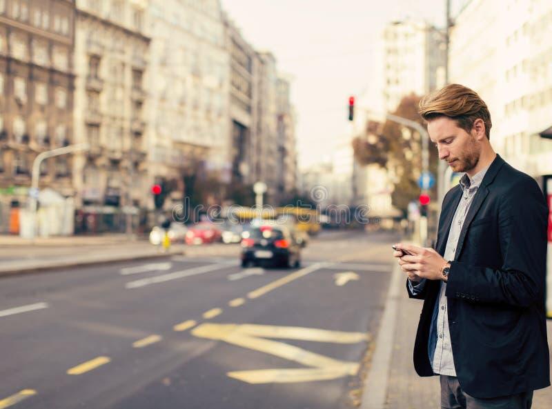 Homme sur la rue avec le téléphone portable images stock