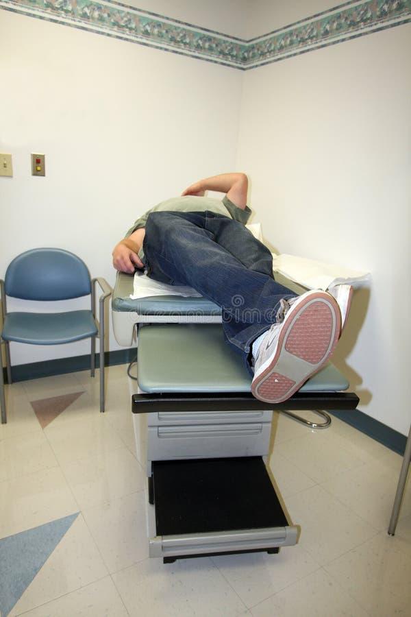 Homme sur la table d'examen dans le bureau du docteur photographie stock