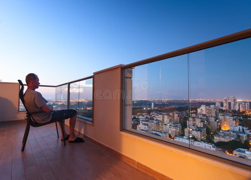 Homme sur le balcon à extrémité élevé dedans en centre ville images stock