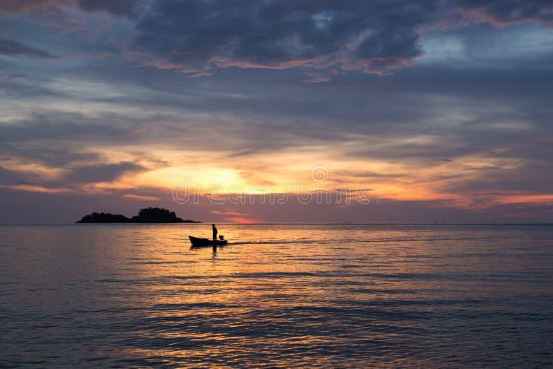 Homme sur le bateau au coucher du soleil images libres de droits