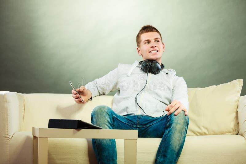 Homme sur le divan avec des écouteurs smartphone et comprimé photos stock