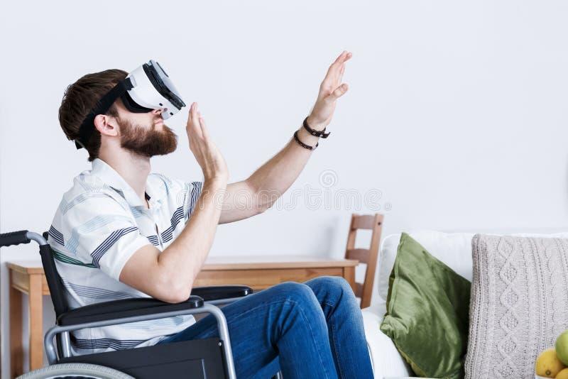 Homme sur le fauteuil roulant dans VR photos stock