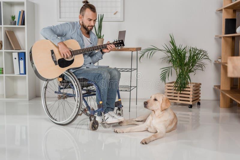 Homme sur le fauteuil roulant jouant la guitare photos libres de droits