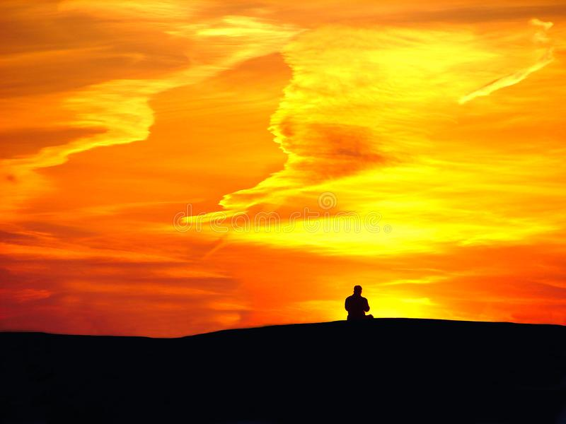 Homme sur le fond de coucher du soleil et le ciel orange photos libres de droits