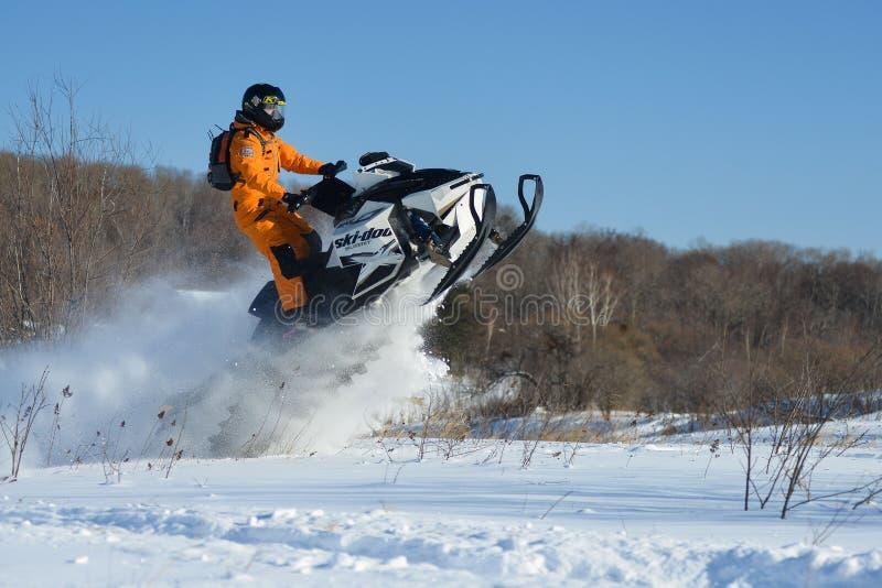 Homme sur le motoneige en montagne d'hiver images stock