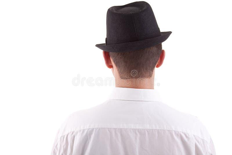 Homme sur le sien en arrière avec un chapeau noir en fonction image stock