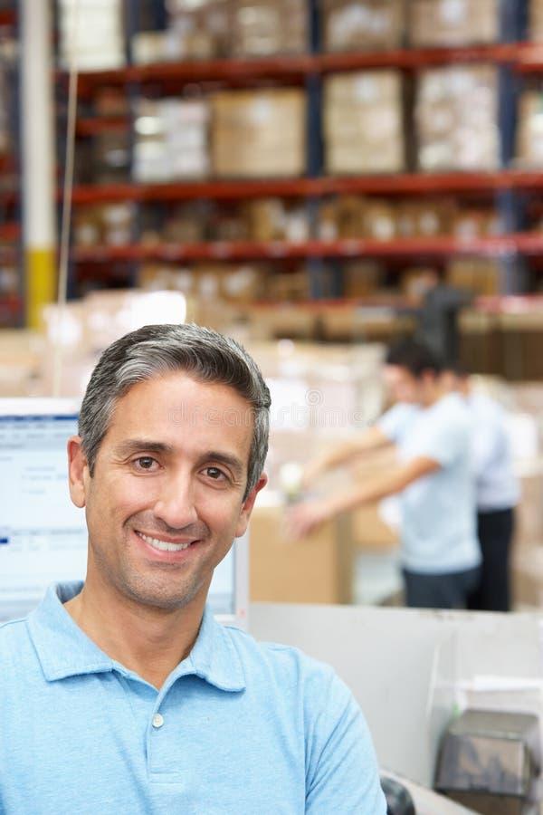 Homme sur le terminal d'ordinateur dans l'entrepôt de distribution images stock