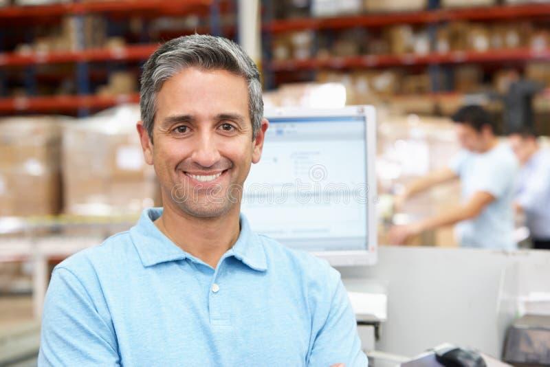 Homme sur le terminal d'ordinateur dans l'entrepôt de distribution image stock