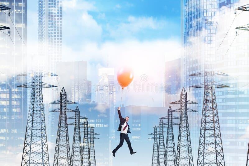 Homme sur le vol de ballon parmi des appuis de ligne électrique photo stock