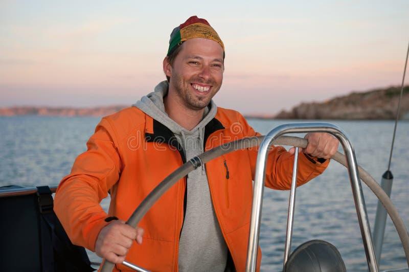 Homme sur le volant de fixation de yacht photos libres de droits