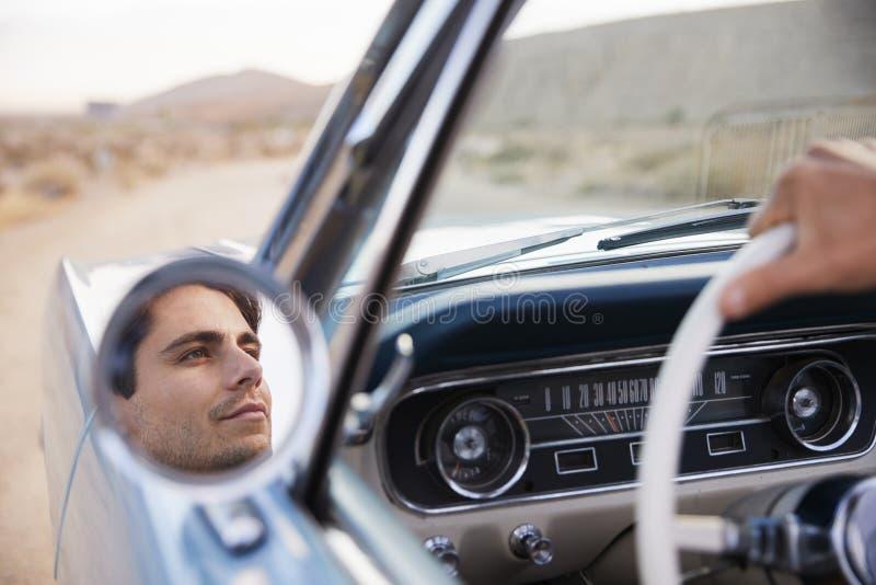 Homme sur le voyage par la route conduisant la voiture convertible classique reflétée en Wing Mirror photographie stock libre de droits