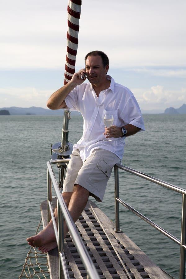 Homme sur le yacht avec le téléphone portable et le vin photos libres de droits