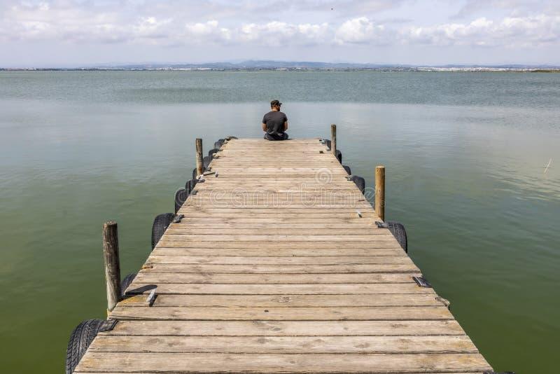 Homme sur un dock par le lac au ciel de matin images libres de droits